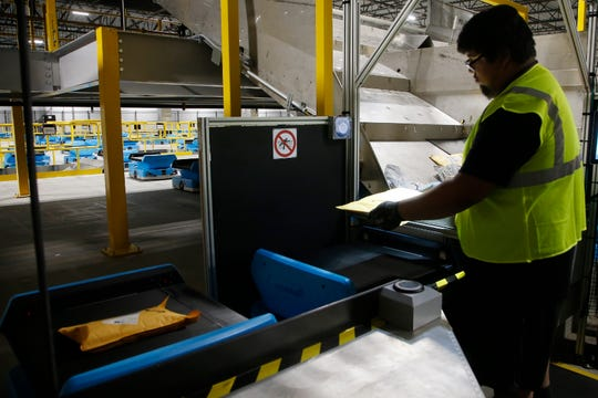 In this Dec. 17, 2019, photo Joseph Salinas places packages onto Amazon robots, transporting packages from workers to chutes that are organized by zip code, at an Amazon warehouse facility in Goodyear, Ariz. Warehouses powered by robotics and AI software are leading to human burnout by adding more work and upping the pressure on workers to speed up their performance, said Beth Gutelius, who studies urban economic development at the University of Illinois at Chicago and has interviewed warehouse operators around the U.S. (AP Photo/Ross D. Franklin)