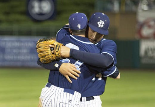 Former Christian Brothers Academy pitcher Luca Dalatri (right) is hugged by teammate Kenny Campbell after he broke the Shore Conference career wins record in the 2016 Shore Conference Tournament championship game.