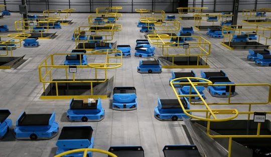 """In this Dec. 17, 2019, photo dozens of Amazon robots transport packages from workers to chutes that are organized by zip code, at an Amazon warehouse facility in Goodyear, Ariz. Amazon and its rivals are increasingly requiring warehouse employees to get used to working with robots. The company now has more than 200,000 robotic vehicles it calls """"drives"""" that are moving goods through its delivery-fulfillment centers around the U.S. (AP Photo/Ross D. Franklin)"""