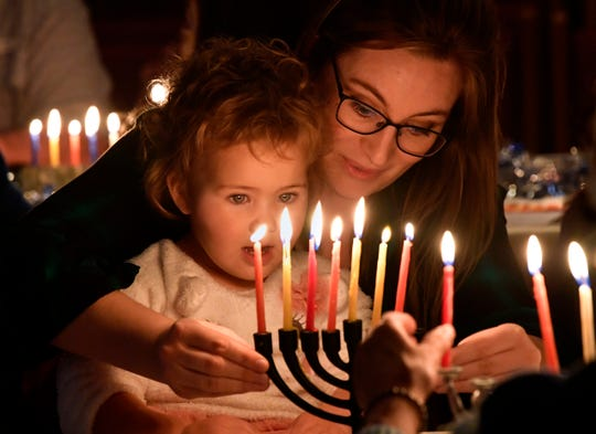 Leslie Moulard lights a menorah with her 2-year-old daughter Moira during Hanukkah festivities at Temple Mizpah Friday.
