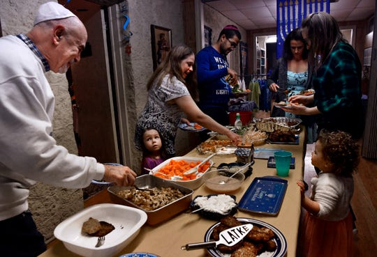 Old and young serve themselves during a Hanukkah potluck meal at Temple Mizpah Friday.