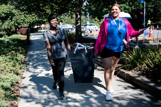 Sharece Hunter, left, of Lincolnton, helps her niece, Cearra Holmes carry her belonging to her dorm room at UNC Asheville during first-year move-in day at the university on Aug. 16, 2019.
