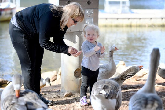 Cheryl Ferguson hands her 20-month-old granddaughter, Ivy Palmer, more bird food as she claps and squeals with delight while feeding the ducks at Lake Julian Park in Arden on Feb. 5, 2019. The weather was unseasonably warm with a high of 68 degrees.