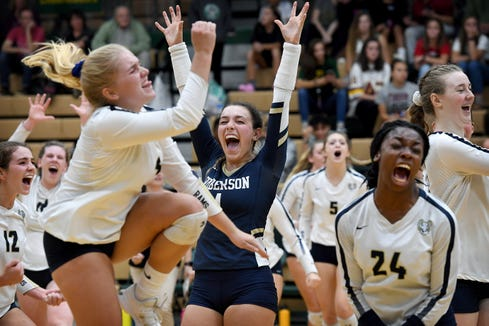 Roberson libero Emerson Hoyle lifts her hands in the air as her teammates celebrate around her after winning their match at Reynolds High School on Oct. 15, 2019.
