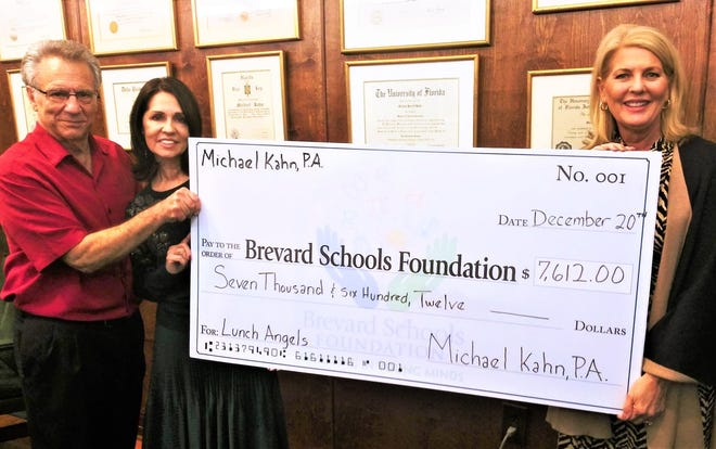 Michael and Roma Kahn (left) present Janice Kershaw, President of the Brevard Schools Foundation, with a check for $7,612 to erase unpaid lunch debt in Brevard County schools.