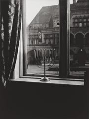 Chanukah Menorah in the window of Rabbi Akova Boruch Posner, opposite the Nazi Party headquarters building in Kiel, Germany, in 1932. The back of the photo was captioned, in German: 'Death to Judah', So the flag says, 'Judah will live forever', So the light answers""