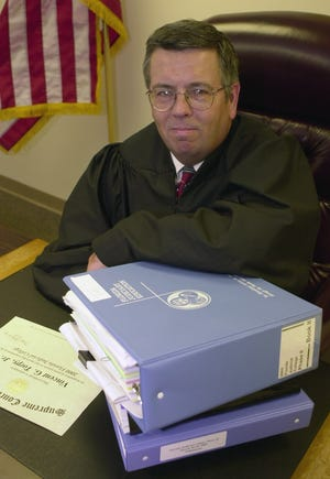 Circuit Judge Vincent Torpy, Jr., in his office at Viera, with his books and diploma from judge school.