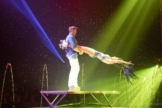 Anita and Karchy Zeman perform amid jets of water in a roller skating act for Cirque Italia.