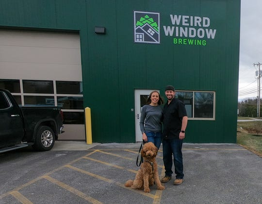 Brewer Jack Droppa, right, stands with his wife, Emily Droppa and dog Citra in front of Weird Window Brewing in South Burlington in early December 2019.