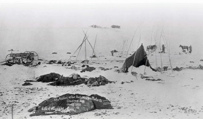 Bodies lie in the snow after the Wounded Knee massacre.