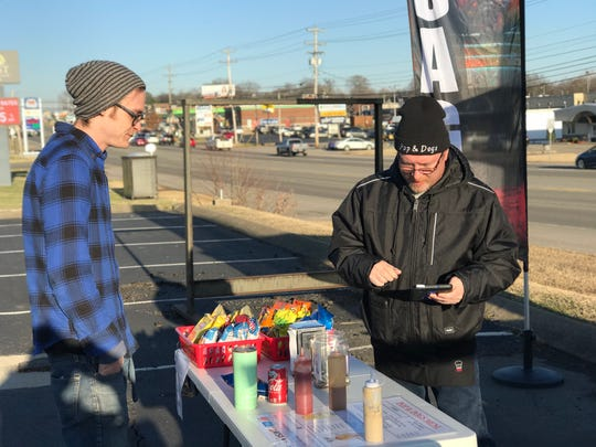 Paul Browning helps a customer at Pops & Dogs hot dog stand.