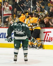 Michigan Tech celebrates the last goal against Michigan State University during the 55th annual Great Lakes Invitational at Little Caesars Arena in Detroit on Monday, December 30, 2019. Michigan Tech defeated Michigan State University 4-2.