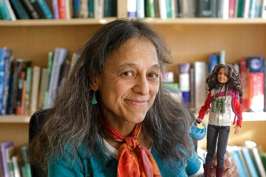 This Dec. 3, 2019, photo, ecologist Nalini Nadkarni is shown in her lab on the University of Utah campus in Salt Lake City holding a Barbie created to look like her when she's climbing into the treetops to study the rainforest canopy.