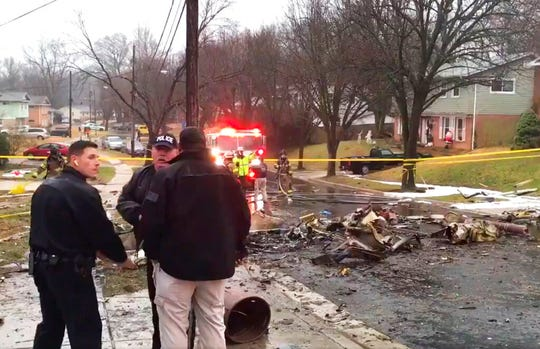 In this image made from video provided by the Prince George's County Fire and Emergency Medical Services Department, firefighters and police officers investigate the scene of a small plane crash in the Lanham neighborhood, Md., Sunday, Dec. 29, 2019.