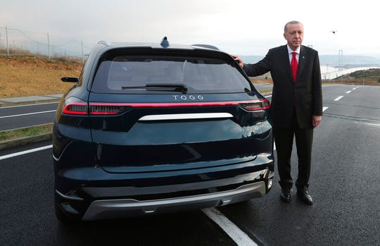 Turkish President Recep Tayyip Erdogan poses with a prototype of a domestically produced electric car, in Gebze, Turkey, Friday, Dec. 27, 2019.
