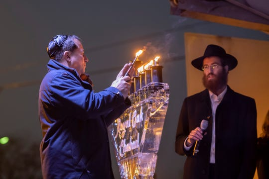 (From left) David Grossman, owner of Pegasus Entertainment, lights a menorah made from ice with Rabbi Moishie Glitsenstein, of the Royal Oak Jewish Center Chabad during an outdoor Hanukkah celebration, in Royal Oak, December 29, 2019.
