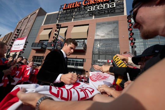 The Red Wings' Dylan Larkin signs autographs outside Little Caesars Arena.