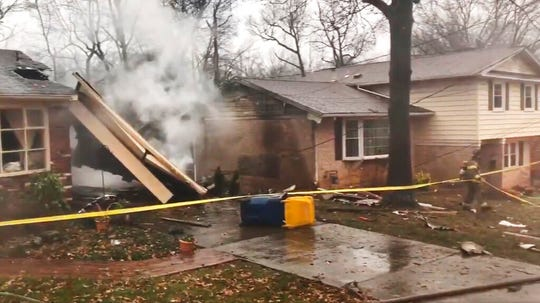 In this image made from video provided by the Prince George's County Fire Department, a firefighter walks around the scene of a small plane crash in the Lanham neighborhood, Md., Sunday, Dec. 29, 2019. The small plane crashed in the Maryland suburbs of the nation's capital Sunday, hitting a home's carport and killing at least a person aboard the aircraft, authorities said.