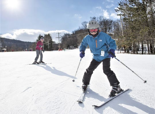 Lingling Wang, left, and husband Xiao Chen of Corning take a run before a first-time lesson on the Alpha slope at Greek Peak Mountain Resort on Jan. 1, 2017.