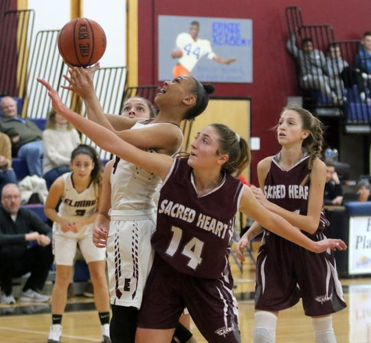 Elmira's Kiara Fisher takes a shot in front of Sacred Heart Academy's Rachel Adolf (14) during the Express' 63-53 win in the girls fifth-place game at the Josh Palmer Fund Elmira Holiday Inn Classic on Dec. 30, 2019 at Ernie Davis Academy.