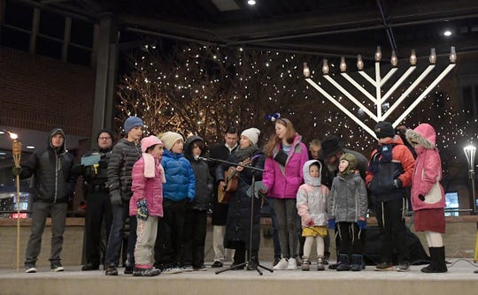 Singers lead the crowd in songs during the annual Menorah Lighting and Chanukah Celebration in Old Town Square in Fort Collins, Colo. on Sunday, Dec. 29, 2019.