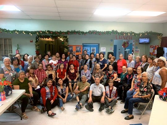"The Guam Sunshine Lions Club visited the Agat Senior Citizens Center on Dec. 18, bringing cheer, song, supplies, and bingo dabbers in the spirit of Christmas and its mission of ""caring for the sick and the elderly."" Members and seniors are shown in the group photo."