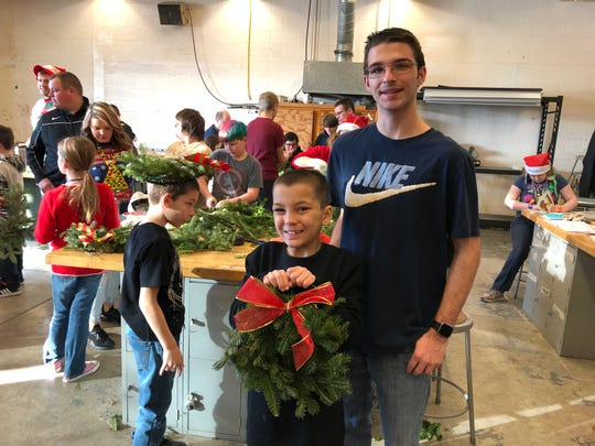 Lucas Bell with his high school partner, Anthony O'Connor, on Community Service Day at the SVE High School. Fourth-graders were partnered with high school volunteers for Santa's Workshop activities. This group made wreaths together with greens donated by local Christmas tree farmer, Don Brock. The kids, big and small, were very proud of their finished wreaths.