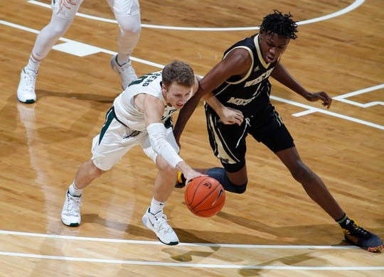 Michigan State's Jack Hoiberg and Western Michigan's Chase Barrs battle for the ball during the first half Sunday.