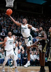 Michigan State's Aaron Henry, center, shoots against Western Michigan's Titus Wright during the first half of an NCAA college basketball game, Sunday, Dec. 29, 2019, in East Lansing, Mich. (AP Photo/Al Goldis)