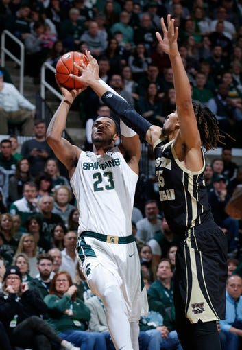 Michigan State's Xavier Tillman, left, shoots against Western Michigan's Brandon Johnson during the first half of an NCAA college basketball game, Sunday, Dec. 29, 2019, in East Lansing, Mich. (AP Photo/Al Goldis)