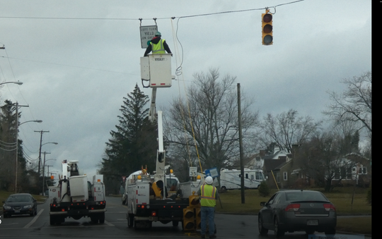 City of Mansfield employees work on a  traffic light at Cook Road and Lexington Avenue on Monday morning as high winds and colder temperatures continued.
