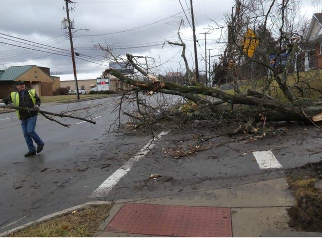 Earnest Putnam with the City of Mansfield clears a tree from Park Avenue West and Shady Lane on Monday.