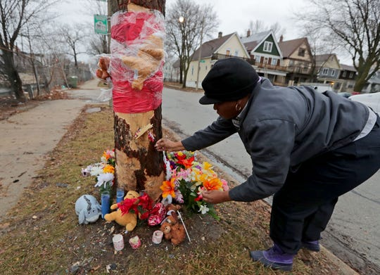 Deahawanda Hurt, of Milwaukee, places a Jesus cross with a Bible scripture to a tree, on Monday, serving as a makeshift memorial at the scene of a single-vehicle crash that left four dead near North 26th and West Townsend streets in Milwaukee on Friday night.
