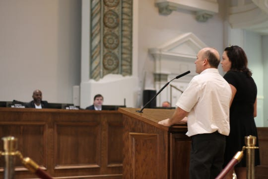 Jerry Cook at the City Council podium with his attorney before the council voted to revoke his business license