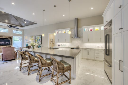 (Kitchen - After): Harwick Homes transformed the residence's kitchen, creating an open and modern space with additional seating and work areas.
