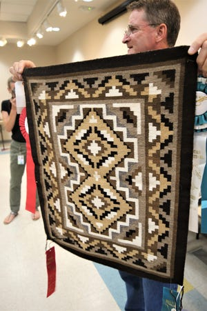 Farmington Museum director Bart Wilsey displays a Two Grey Hills run on Aug. 6, 2019, from a collection of Navajo weavings donated from the estate of the late Bob Culpepper.