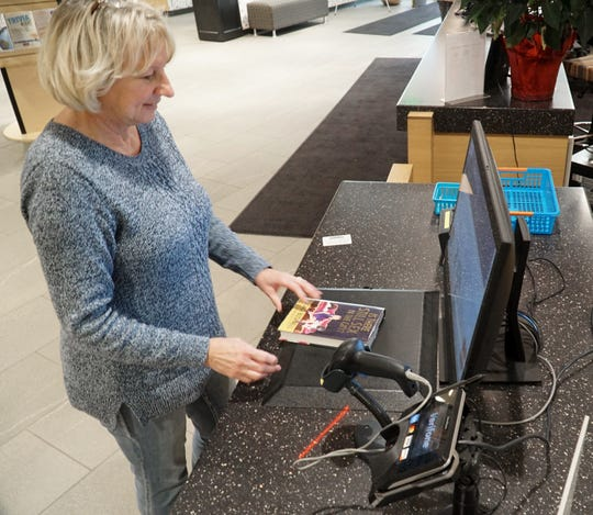 Novi Public Library employee Jean Aldrich checks out a book using the library's sell-checkout kiosk.