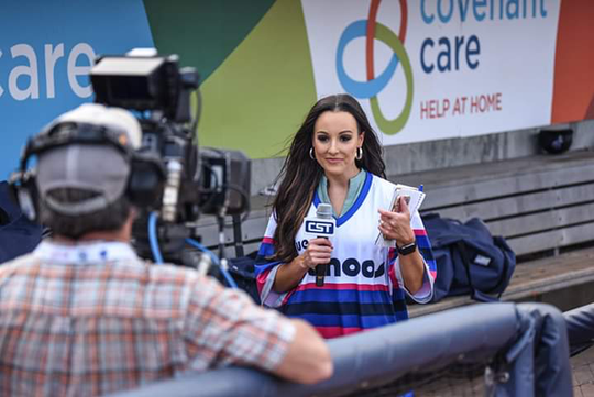 """Carley McCord, working for Cox Sports Television, wears a specialty Blue Wahoos jersey on Aug. 17 during the """"Summer of '69"""" Throwback Night promotion at Blue Wahoos Stadium."""