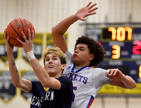 Eastern York's Dustin Cunningham goes to the hoop while covered by Taeshaun Dixon of Spring Grove, Monday, December 30, 2019. 