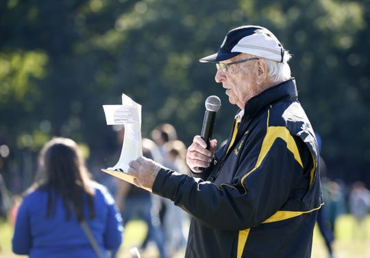 Bob Bradley looks through the schedule as he carries out his announcing duties during the 2018 McQuaid Invitational at Genesee Valley Park.