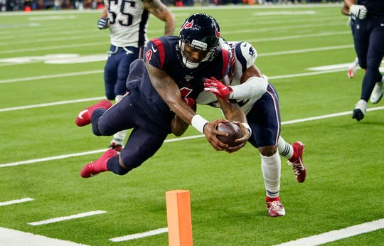 Houston Texans quarterback Deshaun Watson (4) dives past New England Patriots outside linebacker Elandon Roberts (52) to score a touchdown during the second half of an NFL football game Sunday, Dec. 1, 2019, in Houston.