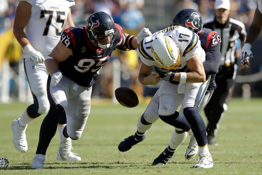Houston Texans defensive end J.J. Watt, left, and outside linebacker Whitney Mercilus, right, force Los Angeles Chargers quarterback Philip Rivers to fumble during the second half of an NFL football game Sunday, Sept. 22, 2019, in Carson, California.