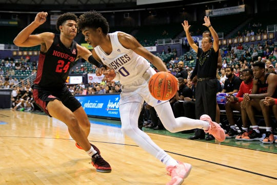 Washington forward Jayden McDaniels (0) tries to get past Houston guard Quentin Grimes (24) during the first half of an NCAA college basketball game Wednesday, Dec. 25, 2019, in Honolulu.