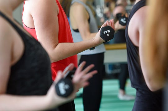 Women pump weights in a barre class on Monday, Dec. 30, at Define: Sioux Falls.