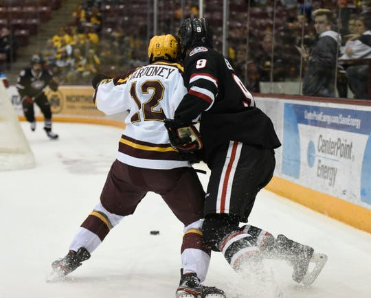 Minnesota's Joey Marooney and St. Cloud State's Spencer Meier fight for the puck Sunday, Dec. 29, 2019, at 3M Arena at Mariucci.