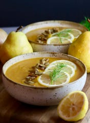 Butternut squash soup is topped with lemon slices and roasted pumpkin seeds.