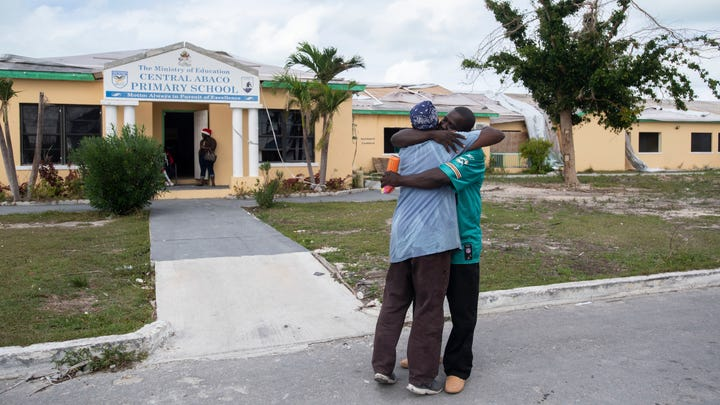 """Paul Mills (left) and Exalise Gue see each other for the first time following the September 1 impact of Hurricane Dorian on Saturday, Dec. 21, 2019, at the Central Abaco Primary School in Marsh Harbour, Bahamas. """"On the 29th of August, we were out eating chicken wings. On September 1st, it was a whole new world. We were just looking for who was alive,"""" Mills said. The damaged school is no longer operating as an education center, but as a makeshift food distribution center."""
