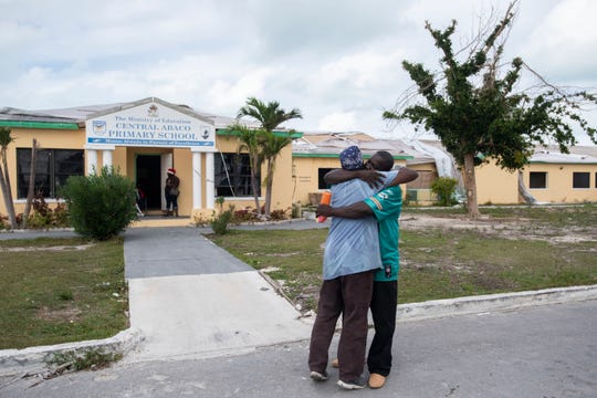 "Paul Mills (left) and Exalise Gue see each other for the first time following the September 1 impact of Hurricane Dorian on Saturday, Dec. 21, 2019, at the Central Abaco Primary School in Marsh Harbour, Bahamas. ""On the 29th of August, we were out eating chicken wings. On September 1st, it was a whole new world. We were just looking for who was alive,"" Mills said. The damaged school is no longer operating as an education center, but as a makeshift food distribution center."