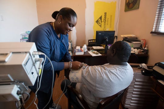 Integrated Medical Centre nurse Chenara Edwards conducts a checkup on patient Ryan Forbes on Saturday, Dec. 21, 2019, at a funeral home turned medical clinic in Marsh Harbour, Bahamas.