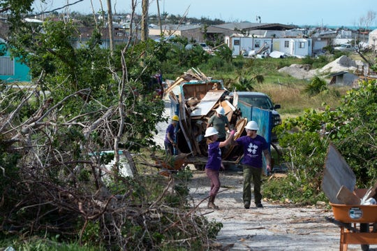 All Hands and Hearts Smart Response volunteers Corynn Benoit (left) and Ryan Ahlberg, both of Salt Lake City, Utah, high five as they remove debris scattered by Hurricane Dorian from a residential property Saturday, Dec. 21, 2019, in Marsh Harbour, Bahamas. The international nonprofit has worked alongside Vero Beach-based Youth on a Mission to clear debris, rebuild and roof homes and clean out moldy walls.